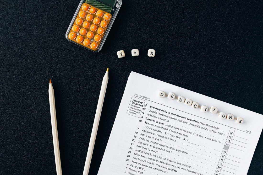 IRS form, pencils, and calculator on a black background