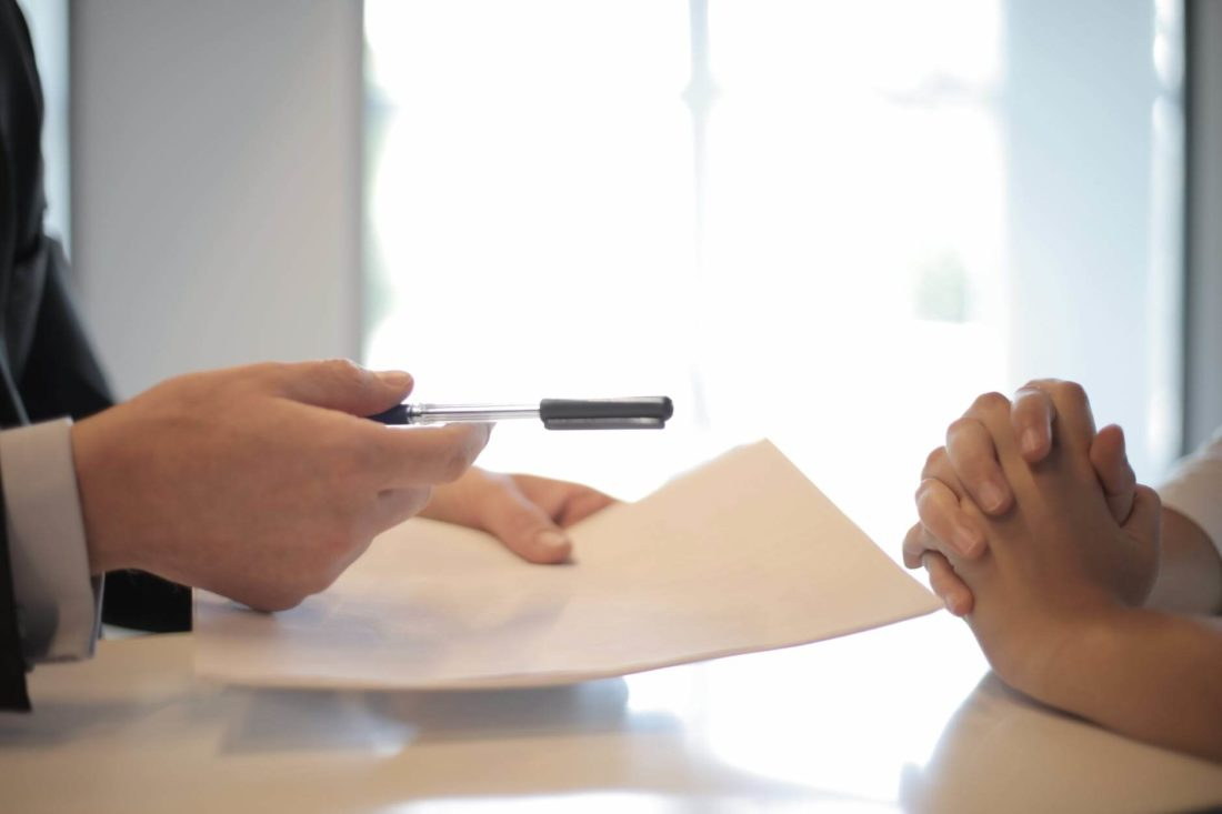 Person signing a contract with a long-distance moving company