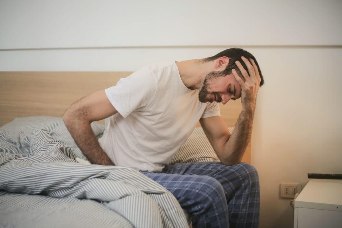 A man is holding his head after long-distance moving