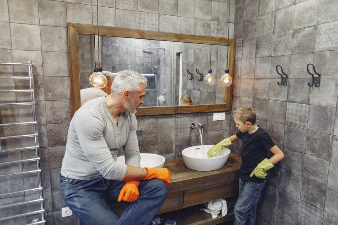 father and son are wearing cleaning gloves cleaning the bathroom sink after cross-country moving